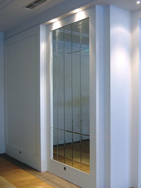 Зеркальное панно с фацетом  на стене из классических прямоугольных зеркальных плиток.