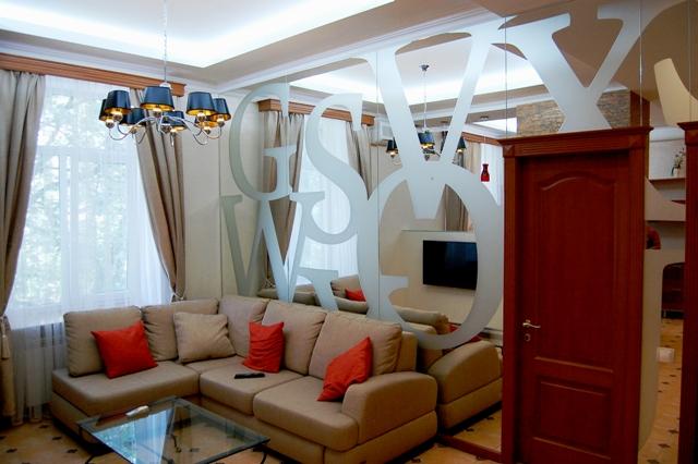 Зеркальная стена в интерьере гостинной комнаты.