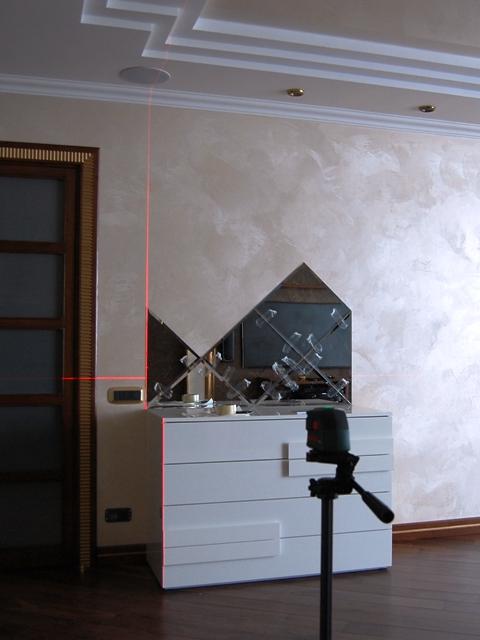 Процесс монтажа зеркального панно с фацетом на стене.